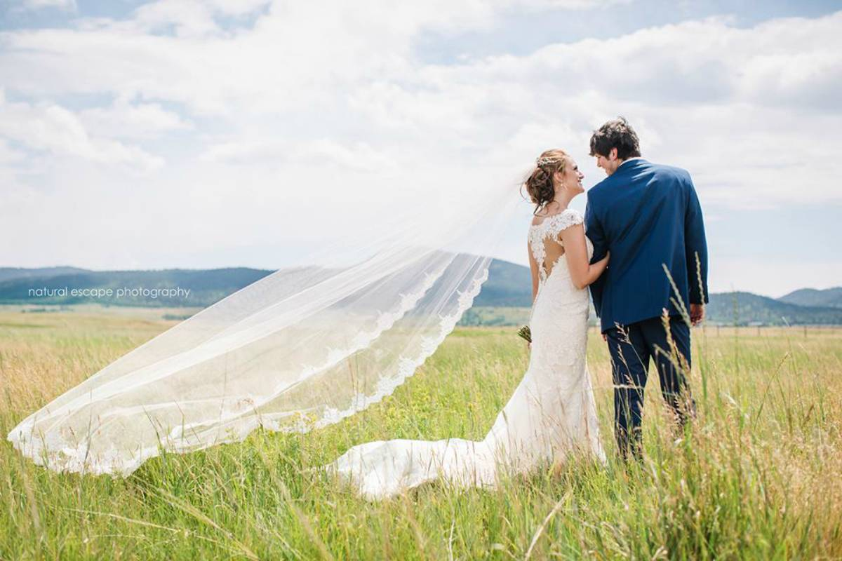 Bride and groom taking a photo in an open grass field with a mountain range in the background