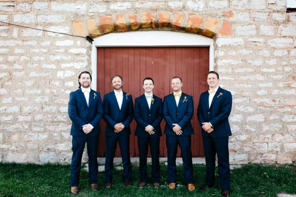 Groom with his groomsmen taking a photo outside of one of our brick barns